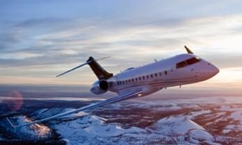 White Bombardier Global 5000 private jet flying over snowy mountains
