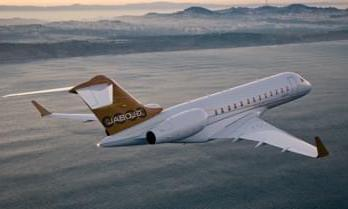 Rear view of a white Bombardier Global 6000 private jet and golden tail over the sea