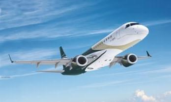 Green Beige and white Embraer Lineage 1000 VIP Airliner flying in a blue sky