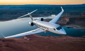 White Gulfstream G650 private jet flying over canyons and lake