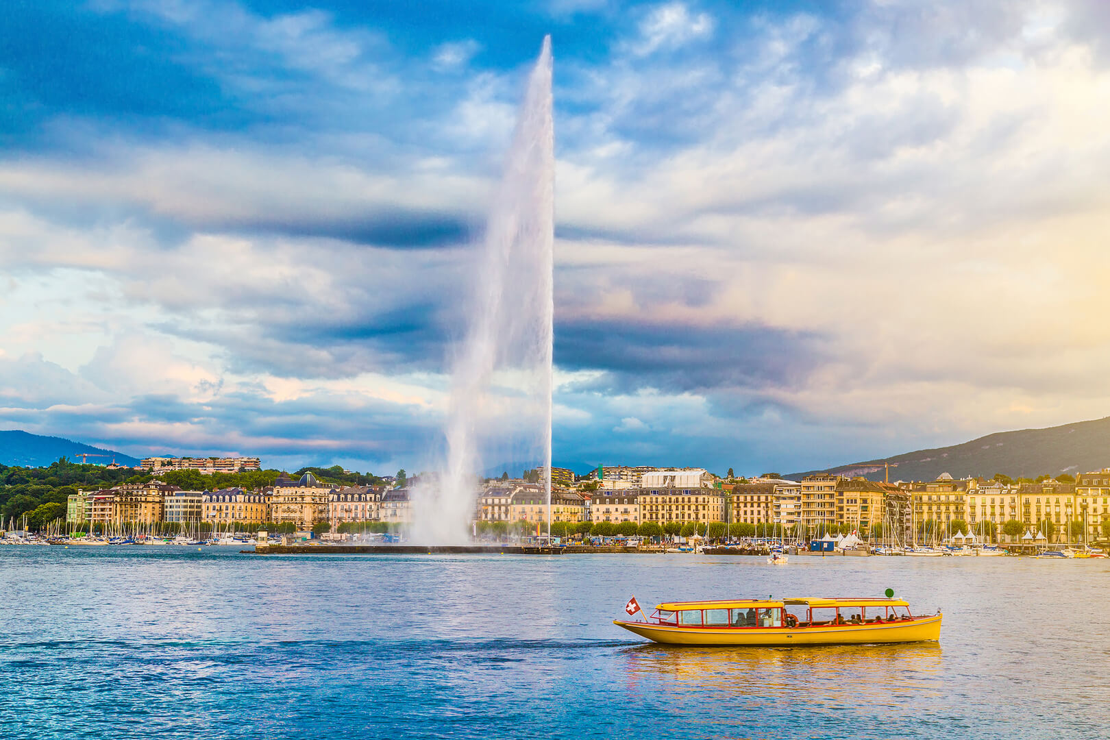 Panoramic view of Geneva skyline with famous Jet d'Eau fountain and traditional boat at harbor district in beautiful evening light at sunset, Canton of Geneva, Switzerland