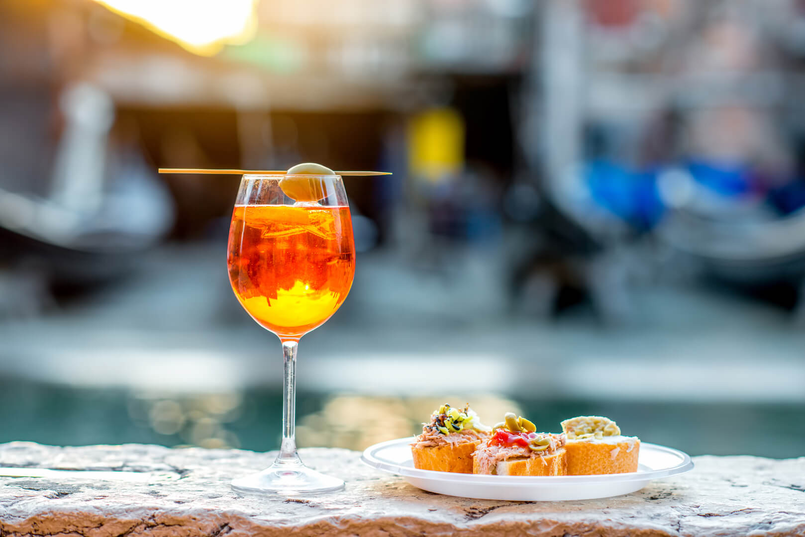 Spritz Aperol drink with venetian traditional snacks cicchetti on the water chanal background in Venice. Traditioanal italian aperitif. Image with small depth of field.