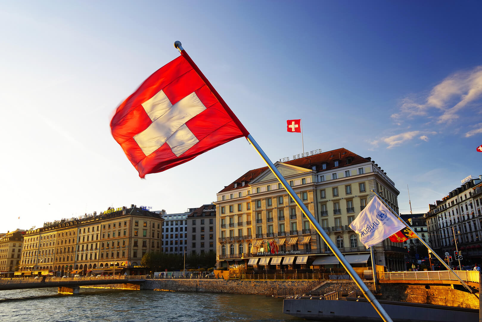 Flag of the Geneva Canton and flag of Switerland in the city center of Geneva on the Mont Blanc Bridge (Pont du Mont Blanc) on the Leman lake