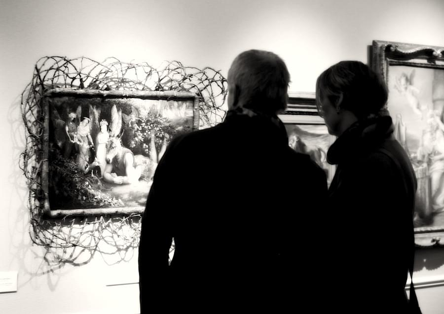 Couple looking at a extraordinary framed painting with a donkey headed human at TEFAF Maastricht