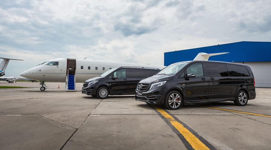 Vans parked alongside a private jet on Vnukovo's airport tarmac