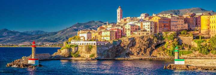 Bastia's lighthouse and colourful houses with sea and mountains in background.
