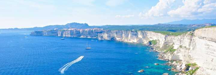 Cliffs of Bonifacio in the south of Corsica with sailboats on a turquoise Mediterranean sea