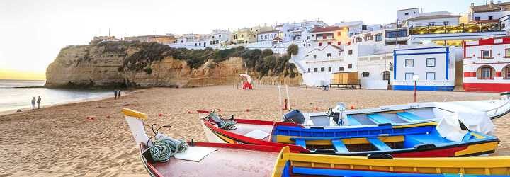 In the foreground the colourful boats on a beach, in the background the white houses with the colourful boride of Faro in Portugal.