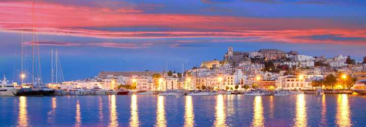 Pink sunset view from boats and yachts in the harbor with the church of Ibiza town