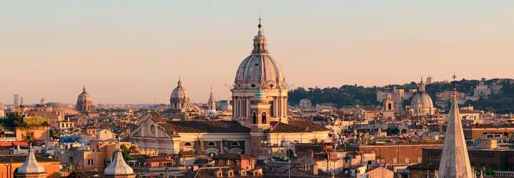 Aerial view of the city of Rome with the dome of Saint Peter's Basilica at sunset