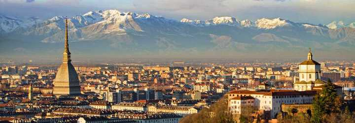Aerial view of the roofs of Turin in Italy at sunset with snow-covered mountains in the background