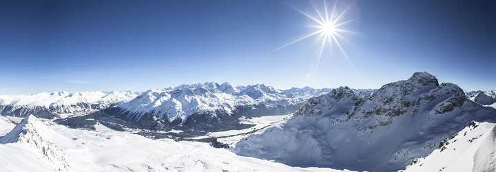 Aerial view of the snowy mountains of Val d'isere ski resort under a blue sky in France
