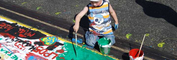 German young boy with a pirate t-shirt painting outside at the Berlin Open Air Gallery