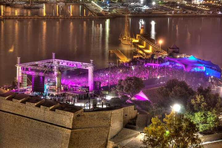 Concert by night illuminated with purple lights at the international music summit in Ibiza city center
