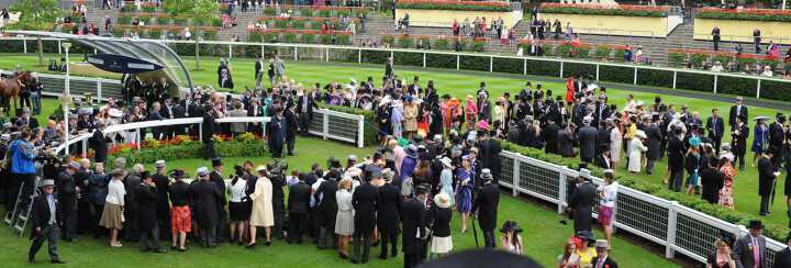 Well dressed wealthy people waiting to admire one of the horses at the Royal Ascot London